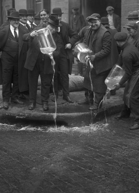 Men pouring out liquor at the start of Prohibition