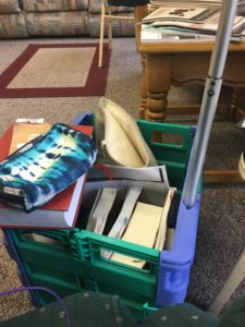 foldable wheelie-crate full of school materials sitting on a carpet