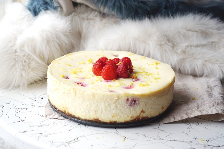 Homemade gluten free lemon, rose and raspberry cheesecake topped with raspberries and lemon zest