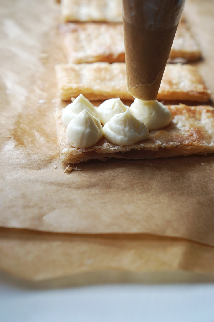 Piping cream cheese frosting onto a slice of puff pastry / how to make mille feuille