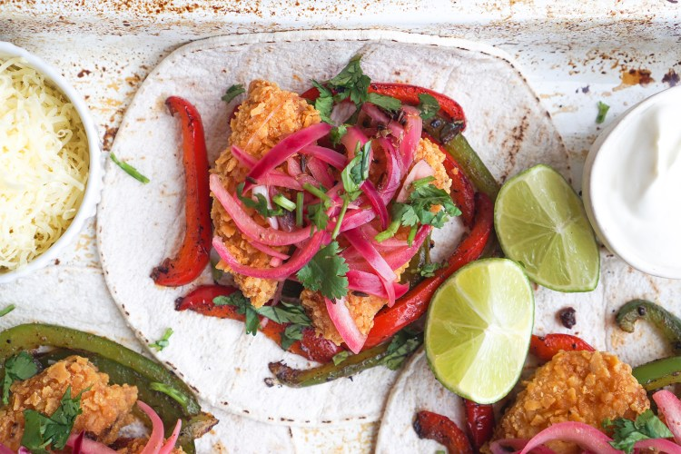 Fried breaded fish tacos with spicy peppers, fresh coriander, lime and Mexican style pickled red onions / on Old El Paso gluten free taco shells