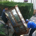 Photo of two Universal Services staff moving  a curio cabinet.