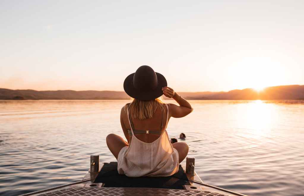 woman sitting on lake pier surrounded by hills at sundown