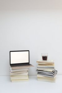 laptop and glass of coffee placed on stacks of books
