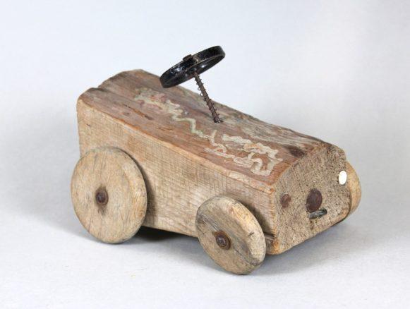 Bildnachweis: Museen der Stadt Nürnberg, Spielzeugmuseum Spielzeug-Auto aus einem Stück Brennholz, 1950er Jahre.