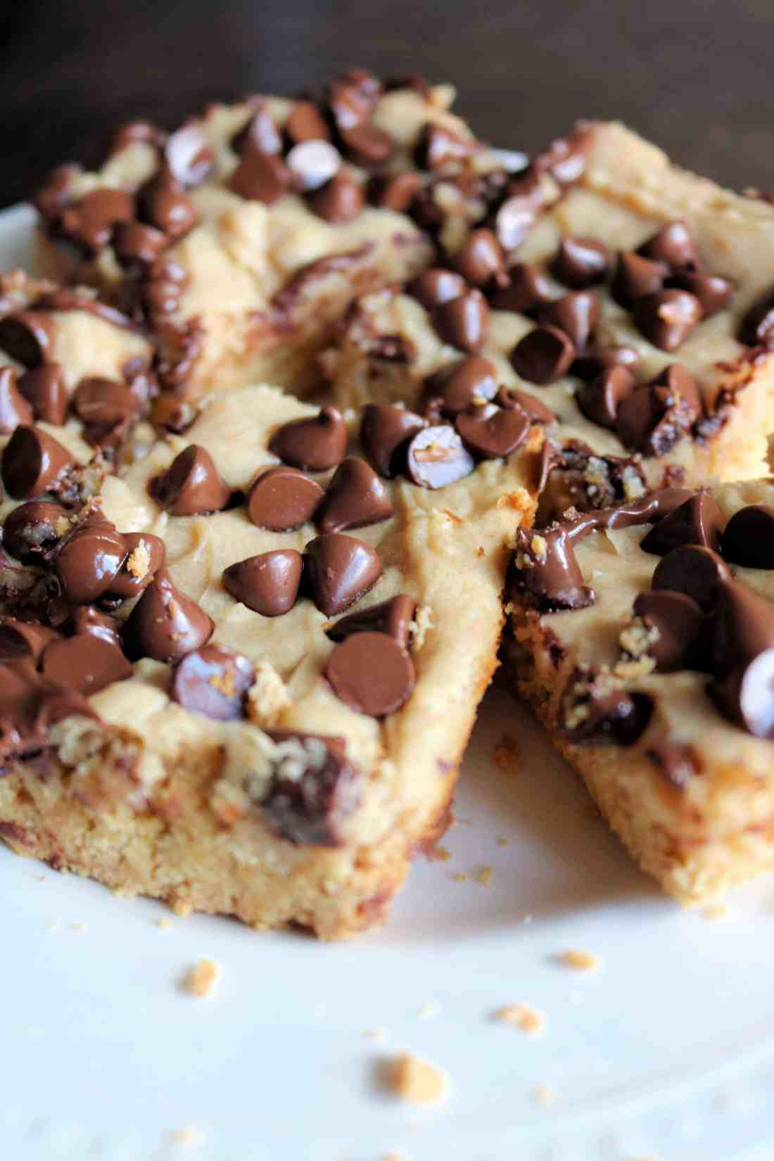 These peanut butter chocolate chip bars are soft, delicious, and packed full of flavor! They bake up in less than 30 minutes with a simple cake mix, creamy peanut butter, cream cheese, and are topped with semi-sweet chocolate chips. #peanutbutterbars #chocolatechipbars #cookiebars