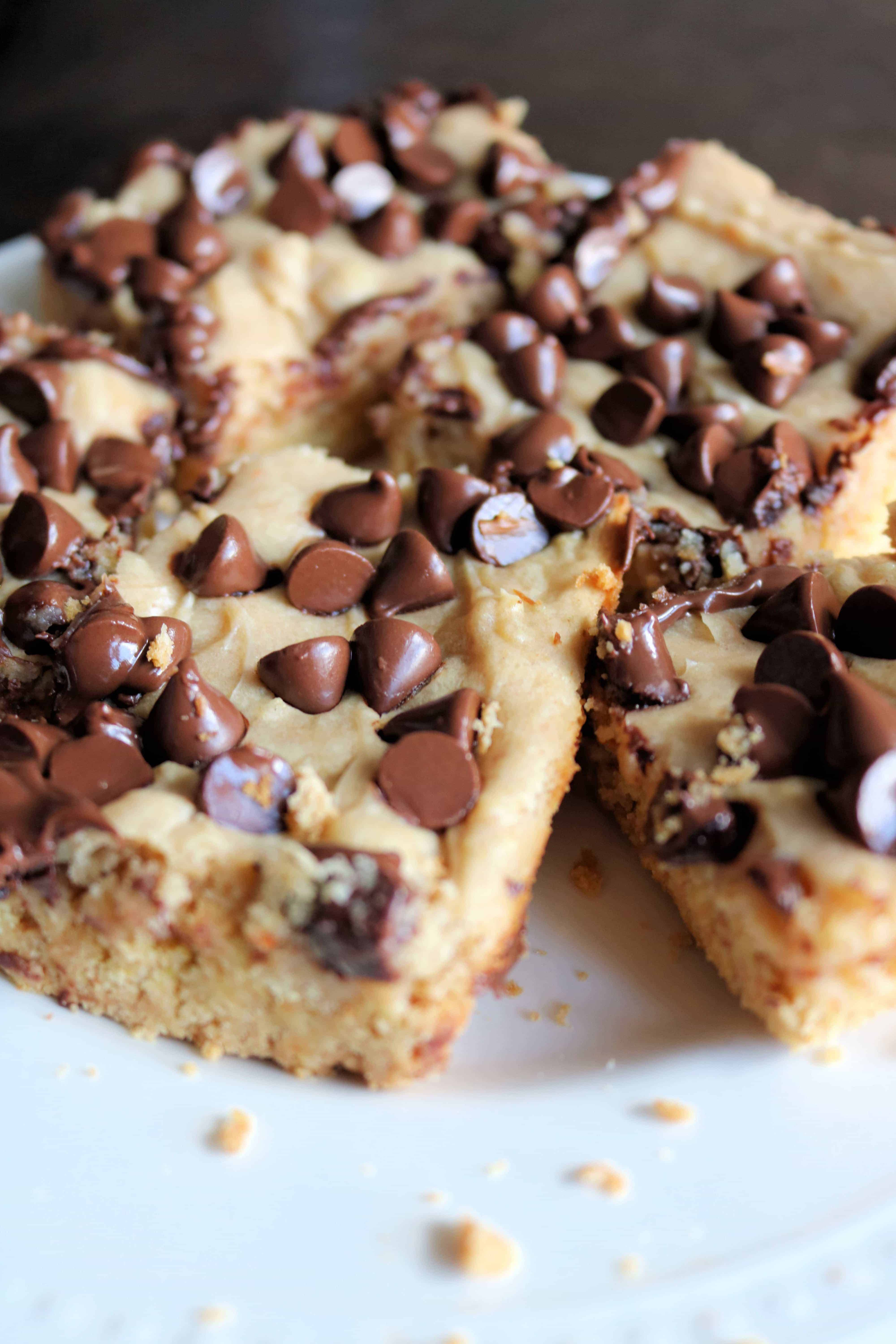 Craving a sweet treat for your family? Try these soft and delicious peanut butter chocolate chip bars! These peanut butter bars are made in a 13x9 pan using a cake mix, creamy peanut butter, cream cheese, and topped with semi-sweet chocolate chips. Even better this easy dessert bakes in less than 30 minutes! #peanutbutterbars #peanutbutter #chocolatechip #cookiebars #blondies #desserts
