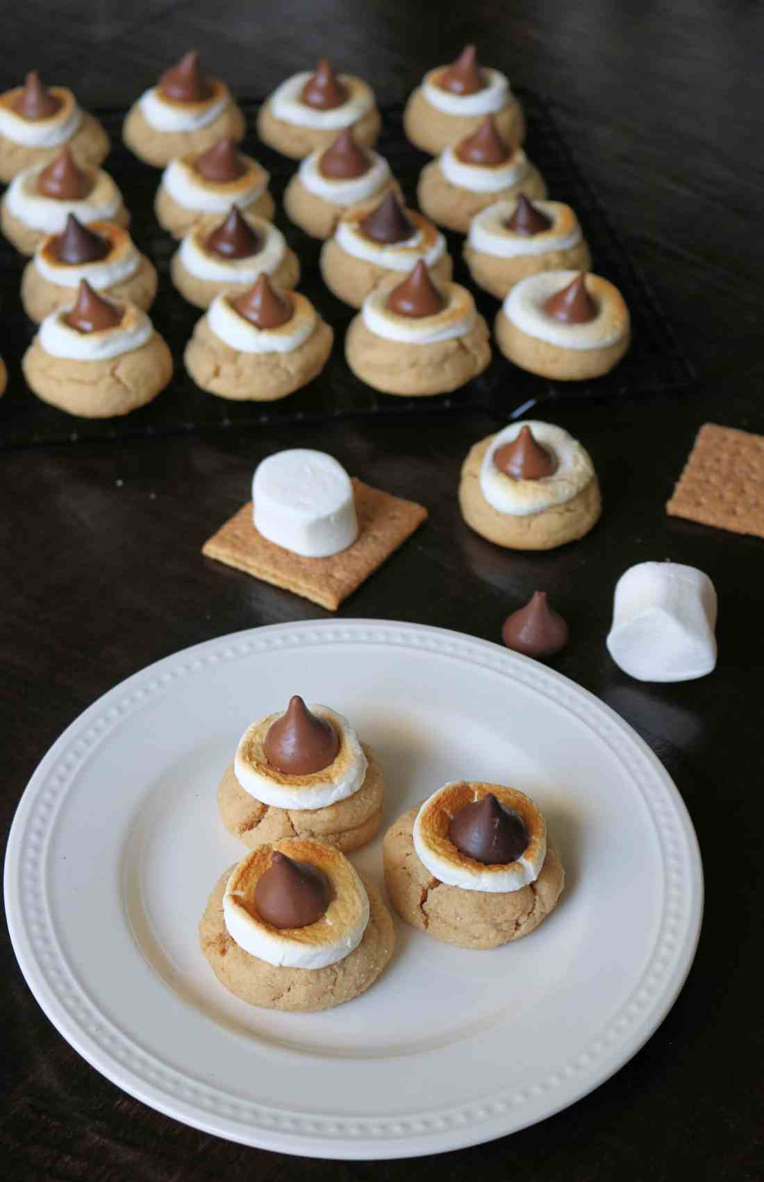 These Easy Hershey Kiss S'mores Cookies are SO good! A graham cracker sugar cookie, marshmallows, and  hershey kisses give these cookies the perfect s'mores flavor! #smorescookies #cookies #baking