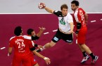 DOHA, QATAR - JANUARY 26: Paul Drux of Germany (2nd R) scores a goal against Ibrahim El Masry (L) , Ahmed Abdelrahman (2nd L) and Ahmed Elahmar of Egypt (R) during the eight final match between Germany and Egypt at Lusail Multipurpose Hall on January 26, 2015 in Doha, Qatar.  (Photo by Christof Koepsel/Bongarts/Getty Images)