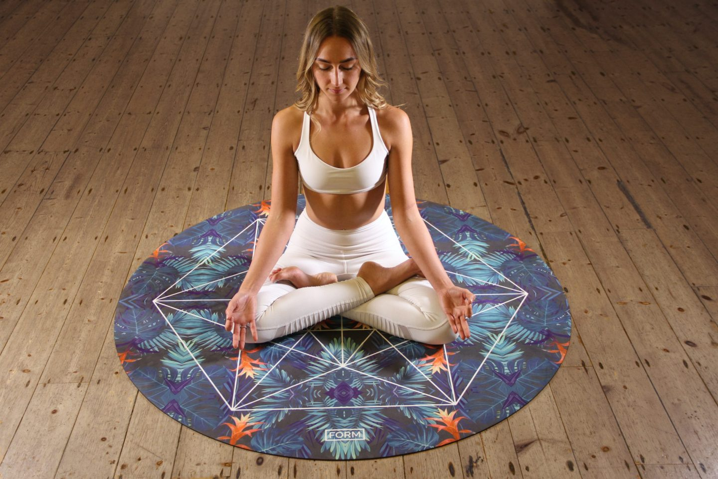 Woman sitting on a round yoga mat, meditating