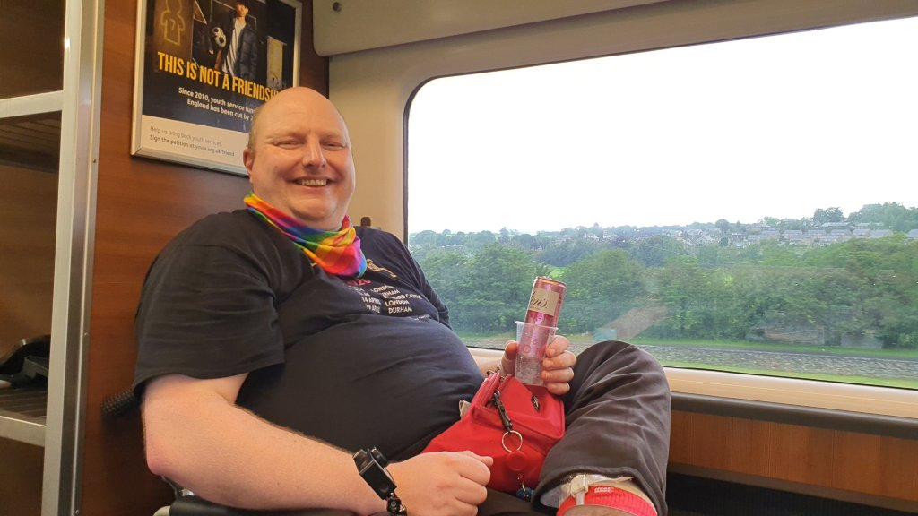 A fast bald bloke is sitting, grinning, on a train, next to a window. He's a wheelchair user