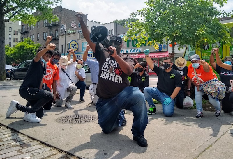 Black Lives Matter Brooklyn Branch President Anthony Beckford leads a black power salute. Photo by Ariama Long