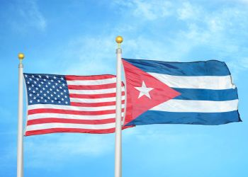 United States and Cuba two flags on flagpoles and blue cloudy sky background