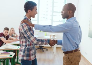 Side view of african american teacher shaking of high school teenage student in clasroom. Stock Photo from 123rf