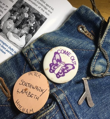 This is an image of three badges pinned to some denim clothing. One badge is made of grey metal in the shape of the Greek letter lambda; another badge is white and depicts a butterfly shape in purple where the body of the butterfly is replaced by a raised fist and displays the words 'COME OUT'; another badge is of brown paper or card and has the words, 'PETER / SOUTHWARK/LAMBETH / HITCHAM' written onto it in black pen. To the right of the denim is a black and white photograph of Oliver Merrington (on the left) aged 23, and Peter Hitcham aged 21. Oliver and Peter are sitting on grass and Oliver has a balloon at his feet which displays the words 'GLAD to be GAY'.
