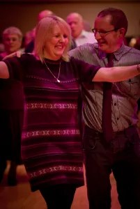 a couple on the dance floor in the middle of a dance move where they are parallel to each other. Both are smiling and llok like they are enjoying dancing.