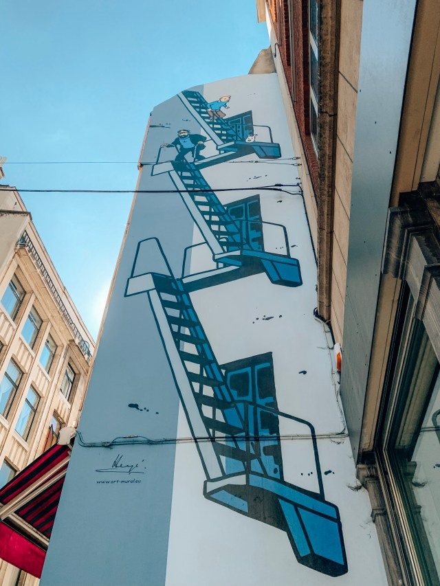 A mural showing Tintin and friends descending a set of stairs, part of the Brussels Comic Book Route