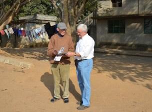 Guido geeft een gedrukt exemplaar van onze eindejaarsbrochure aan pater Louis die hem aandachtig bekijkt.