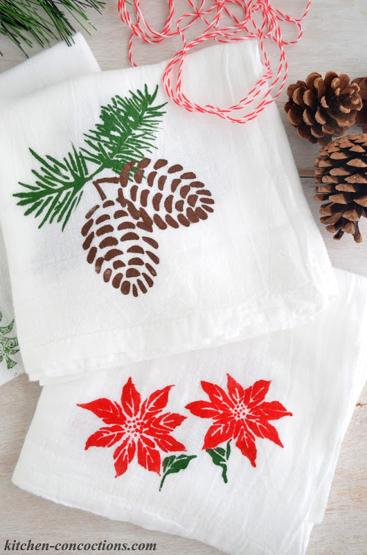 white tea towels hand stamped with pinecones and poinsettias with real pinecones and red twine on the side
