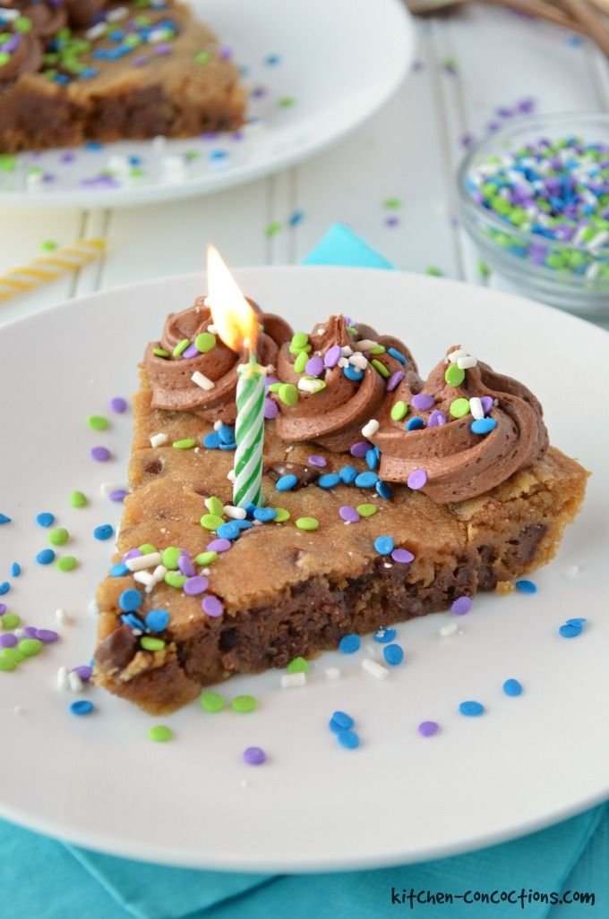 Chocolate Chip Cookie Cake with chocolate frosting, blue, purple and white sprinkles. Served on a white plate with blue napkins and a candle.