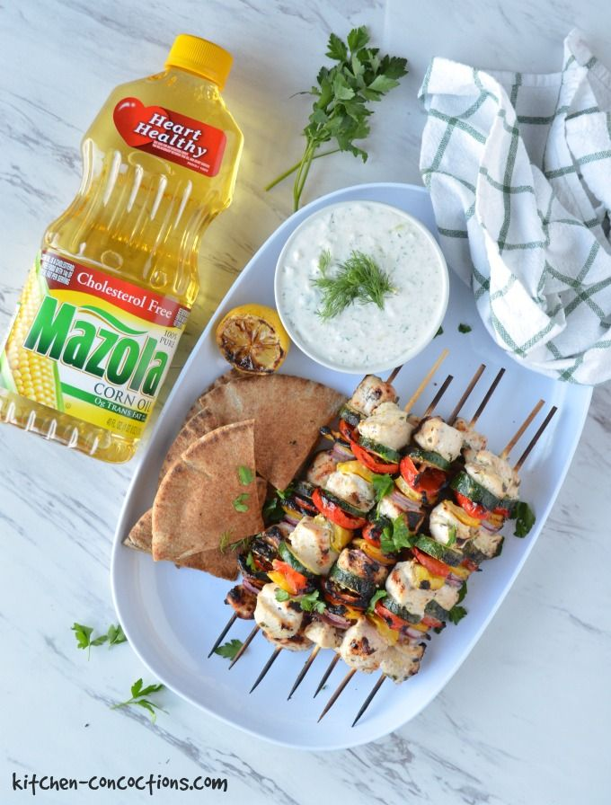 An overhead photo of Greek Chicken Kebabs on a white serving platter with a side of grilled pita bread, grilled lemon wedges and a bowl of Homemade Tzatziki Sauce. A green and white striped towel and a bottle of Mazola Corn Oil is lying is next to the platter.