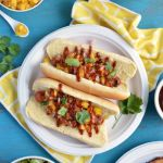 Hawaiian Hot Dogs image with a mango and pineapple relish in a small white bowl, grilled hot dogs in hot dog buns on a white paper plate topped with the relish and fresh cilantro. Also, other food as part of a grilling spread including grilled chicken, macaroni salad and chopped salad.