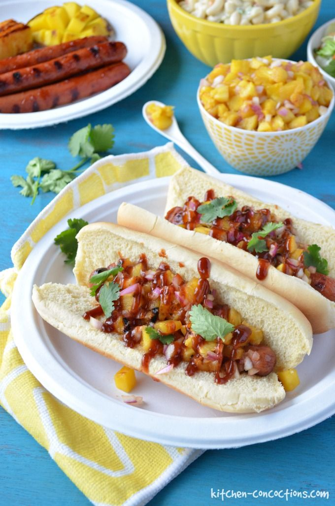 Hawaiian Hot Dogs image with a mango and pineapple relish in a small white bowl, grilled hot dogs in hot dog buns on a white paper plate topped with the relish and fresh cilantro