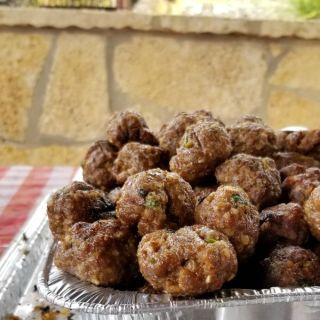 grilled lamb meatballs in a metal pan on a picnic table