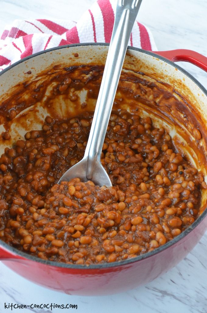 root beer baked beans in a large red dutch oven pot with a metal spoon and red and white striped towel