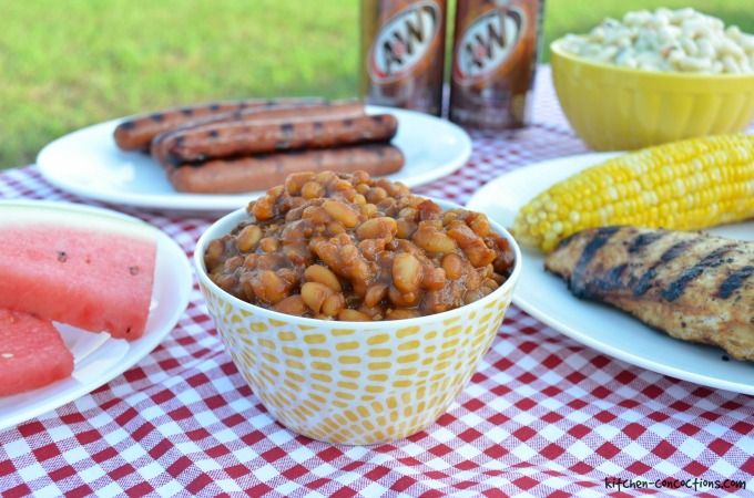 root beer baked beans in a red dutch oven pot on a picnic table with a red gingham tablecloth with watermelon slices, grilled hot dogs, macaroni salad, grilled corn on the cob, grilled chicken and cans of A&W Root Beer