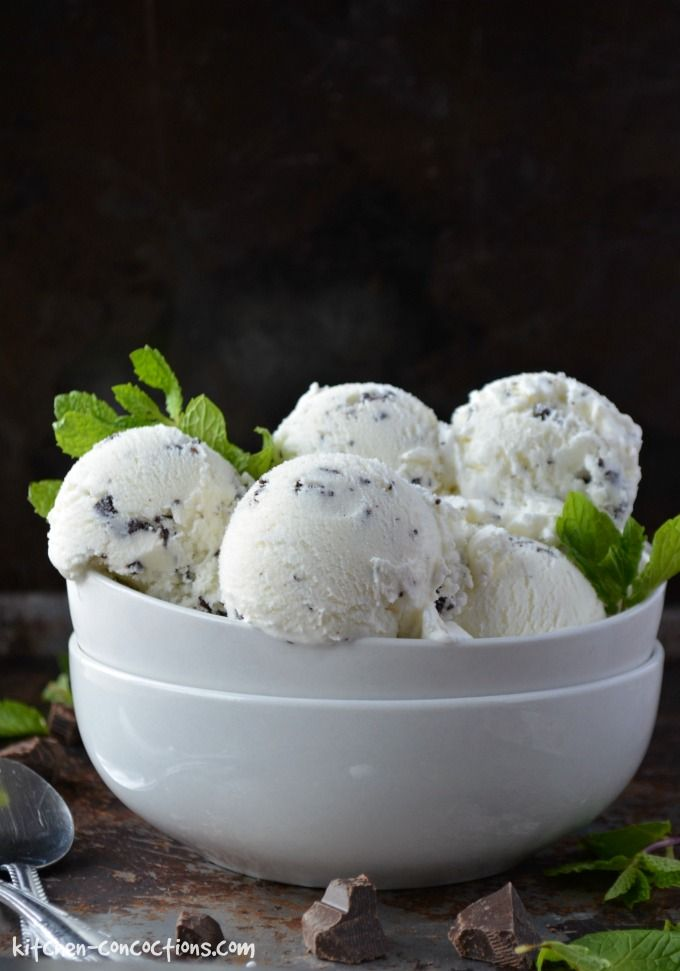 Fresh Mint Stracciatella Gelato in a white bowl with sprigs of fresh mint on a dark background with silver spoons on the side.