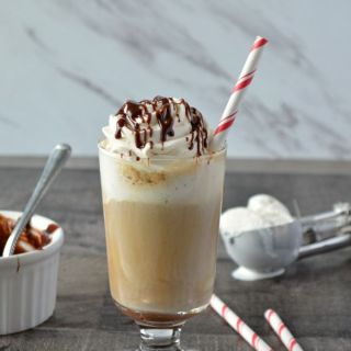 Mocha Root Beer Float in a tall dessert glass topped with whipped cream and a drizzle of chocolate sauce and served with a red and white paper straw.
