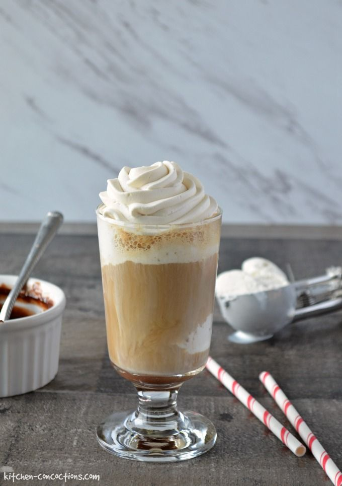 Mocha Root Beer Float in a tall dessert glass topped with whipped cream. Red and white paper straws are on the counter beside the glass and a bowl of chocolate sauce is in the background.