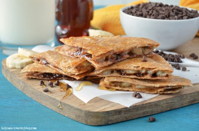 Peanut Butter and Banana Quesadillas cut into quarters, drizzled with honey and served on a cutting board placed on a teal backdrop. A glass of milk, honey bear and bowl of mini chocolate chips are in the background.