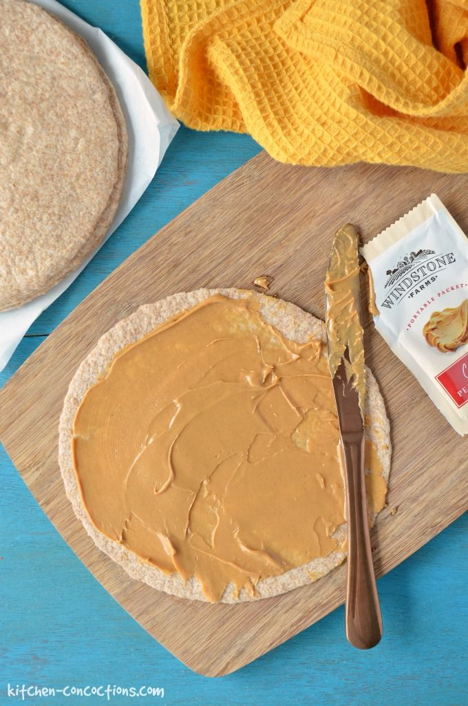 A whole wheat tortilla on a cutting board with peanut butter on top and a Windstone peanut butter packet on the side.