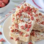 Strawberry Rice Krispie Treats stacked on a white plate with a glass of milk, red and white towel and bowel of dried strawberries in the background.