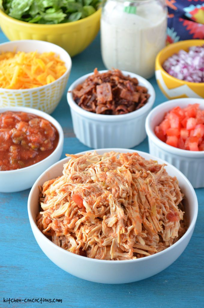 Shredded salsa ranch chicken in a white bowl on a blue backdrop with additional white bowls filled with other taco toppings like salsa, cheese, red onions, tomatoes, etc.