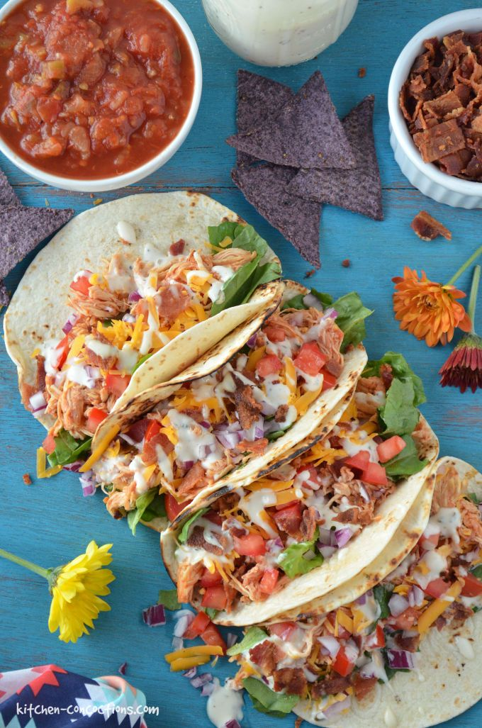 overhead photo of four assembled Chicken Ranch Tacos with a blue corn tortilla chips, bowl of salsa, jar of ranch dressing.