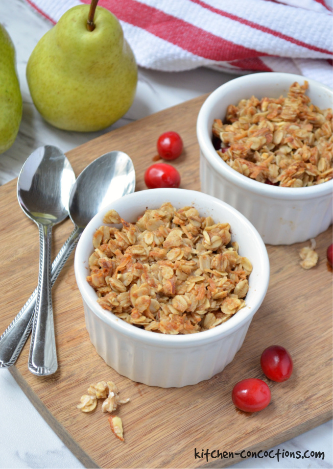 Cranberry Pear Crisp in a white ramekin sitting on a wooden cutting board with a spoon next to it.