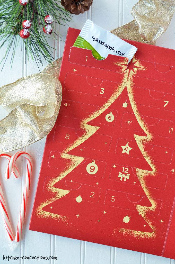 a tea advent calendar in a red box with a gold Christmas tree on the box with gold ribbon, candy canes and pinecones for decorations