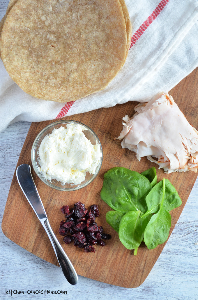 Ingredients for a Turkey Cranberry Wrap on a wooden cutting board.