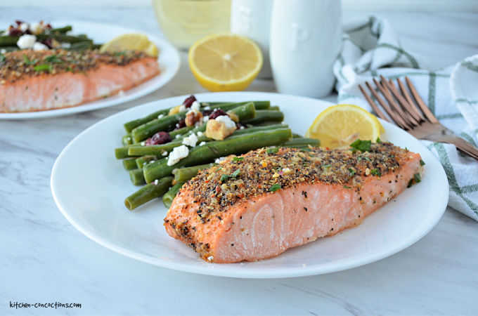 a white plate with a piece of lemon pepper salmon, a side of green beans, fresh lemon slices and a green and white striped towel, whole lemon, glass of white wine, two gold forks and a white salt and pepper shaker on the side