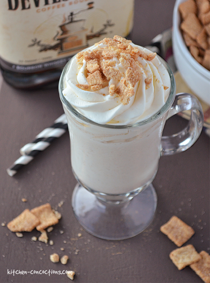 Coffee Cinnamon Toast Crunch Milkshake served in a milkshake glass with two black and white striped straws, on a brown board with a white bowl filled with cinnamon toast crunch cereal and a bottle of coffee bourbon in the background