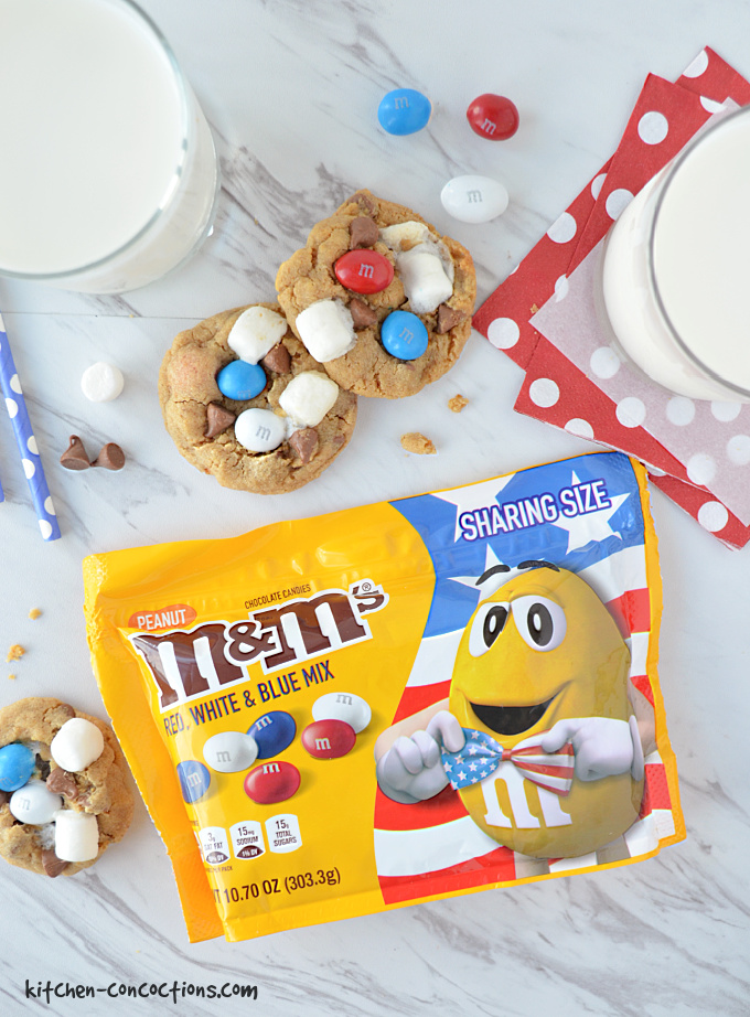 Peanut Butter S'mores Cookies on a marble background with a bag of Red, White and Blue Peanut M&M's lying next to the cookies. There are also two glasses of milk with one glass of milk sitting on top of a red cocktail napkin with white polka dots.