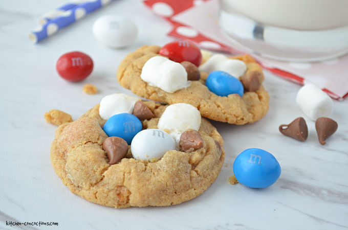 Two Peanut Butter S'mores Cookies sitting on a marble counter next to a glass of milk with chocolate chips, marshmallows and red, white and blue M&M's scattered around the side of the cookies.