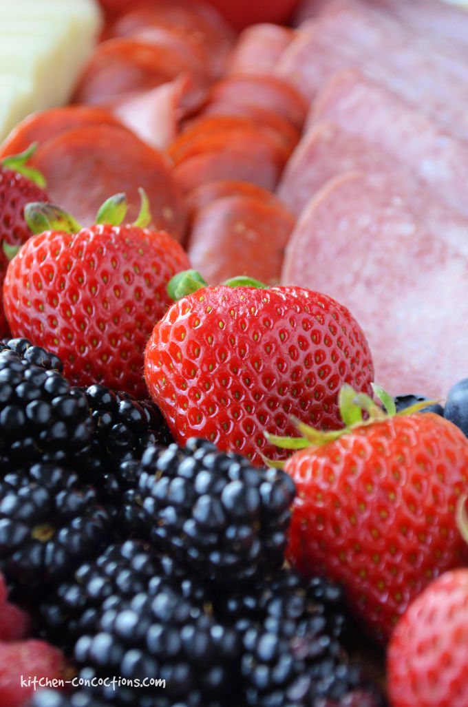 close up photo of blackberries, strawberries, pepperoni and salami slices