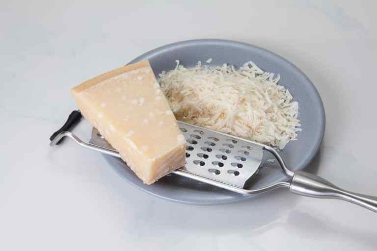 ganzer und geriebener Parmesan mit Reibe