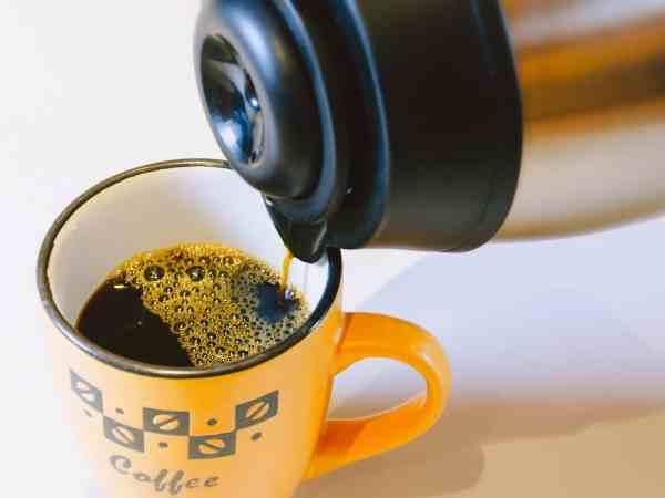 Kaffee wird aus Thermoskanne in Becher gegossen