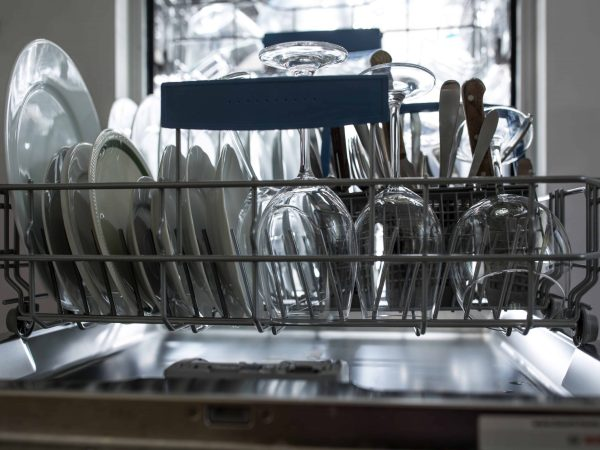 Open dishwasher with clean glass and dishes selective focus Clean glasses after washing in the dishwasher.