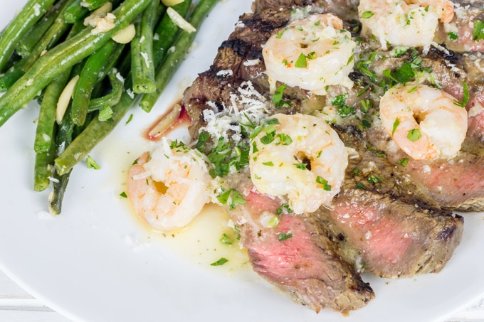 Grilled ribeye steak that's marinated in garlic and herb infused buttermilk, then topped with garlic shrimp scampi.